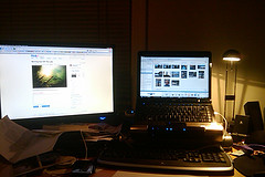 Two online computer monitors in a dim room
